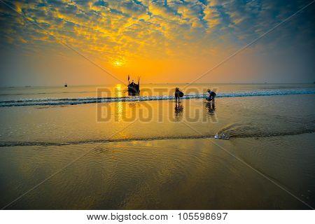 People work on a beach in sunrise