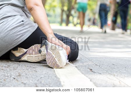 Sports injury. Woman with pain in ankle while jogging in the park poster