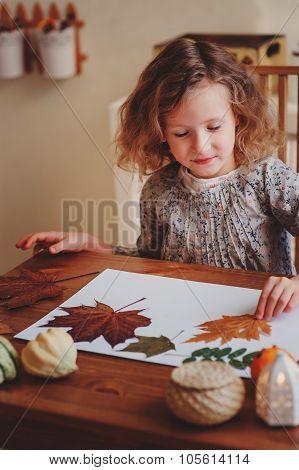 cute child girl making herbarium at home, autumn seasonal crafts
