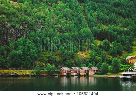 Red wooden docks in small tourist town of Flam on western side of Norway deep in fjords. Forest Background poster