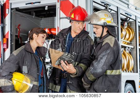 Male firefighter showing clipboard to colleagues against truck at fire station