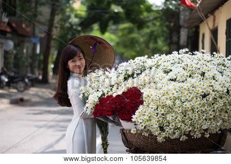 Vietnamese girl in traditional dress buying white daisy flower on street in Hanoi