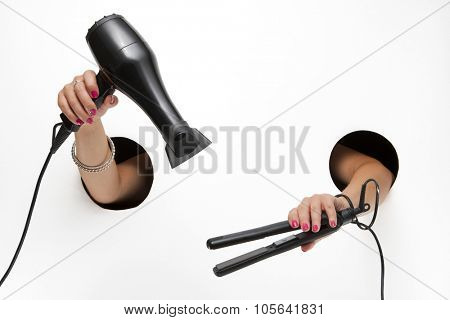 Female barber with hairdryer and curling iron in a hands through the holes on a white background