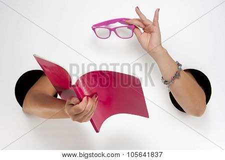 Female  hands through the holes on a white background are holding a pink book and glasses