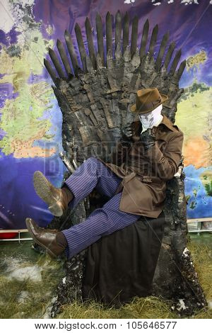 MOSCOW - OCT 12, 2014:  Cosplay Rorschach in the white mask and hat sitting on a brown coat black throne at the EveryCon 2014 in the exhibition center Sokolniki
