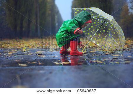 Toddler And Umbrella In Autumn Rainy Park