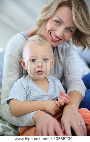 Baby boy sitting on mommy's lap poster