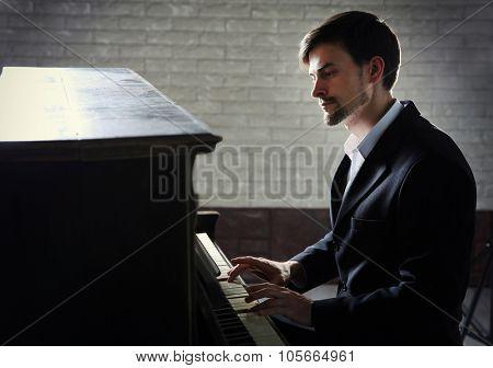 Handsome man in black suit plays piano in the studio