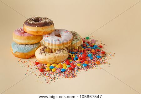 Party decoration. Donuts with colored dragee on cream backgrount copy space poster