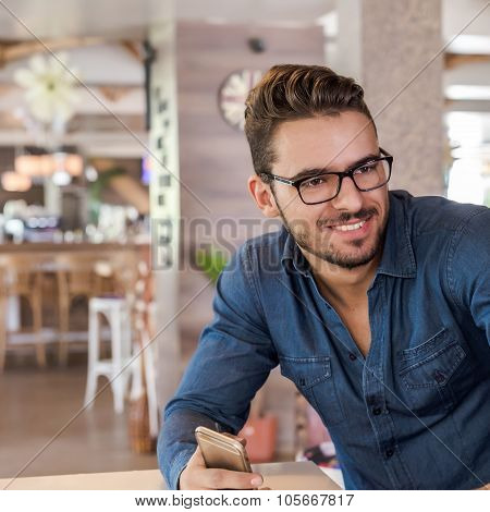 Smiling Handsome Man With Eyeglasses And Smartphone In Hand