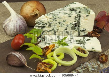 Cheese with mold on a wooden cutting board. Preparation of aromatic cheese