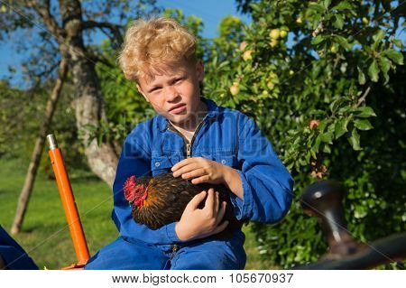 Farm boy with chicken riding on orange tractor