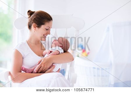 Mother And Newborn Baby In White Nursery