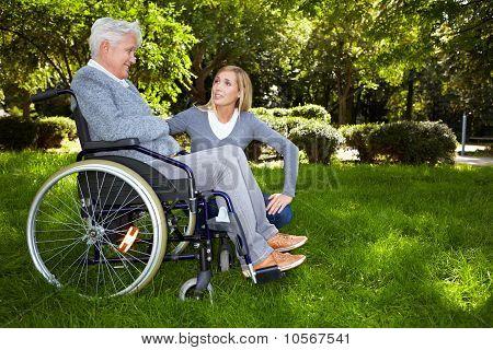 Nurse Talking To Woman In Wheelchair In Park