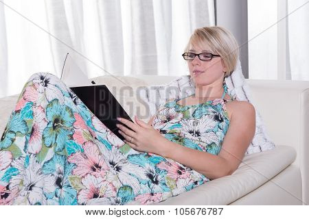 Young Attractive Woman In Summer Dress Is Reading On The Couch