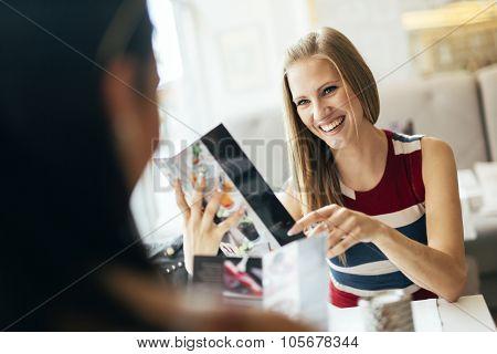 Beautiful Women Looking At Menu In Restaurant