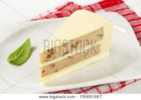close up of unbaked nut cake slice on white square plate and checkered dishtowel