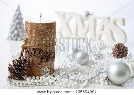 Natural christmas still-life with candle, pineal and ornaments.
