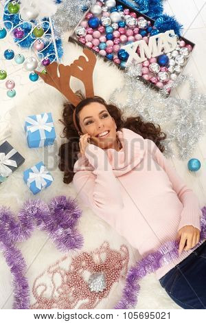Young woman talking on mobilephone, lying on floor at xmas, wearing reindeer antler, smiling happy.