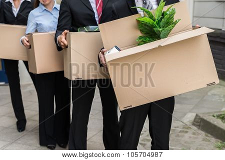 Close-up Of Unemployed Businesspeople Carrying Cardboard Boxes poster
