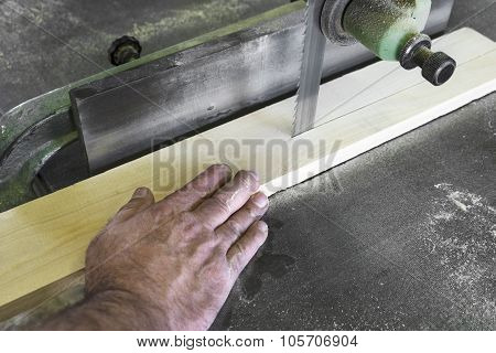 Carpenter Cutting Piece Of Wood With Bandsaw In Workshop