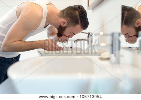 Man Rinsing His Toothbrush Under Running Water
