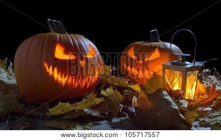 Spooky Jack O Lantern Among Dried Leaves On Black