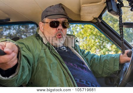 Portrait of senior driver making popular selfie in a shabby car