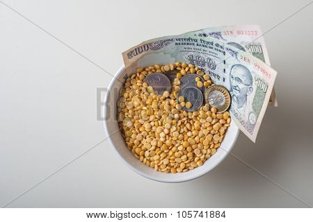 Price rise in basic food and pulses in India. 100 Rupees currency notes and coins in the bowl of Tur Dal.