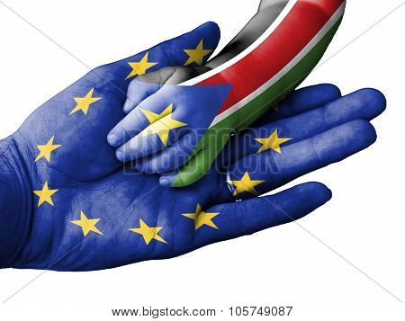 Adult Man Holding A Baby Hand With European Union And South Sudan Flags Overlaid. Isolated On White