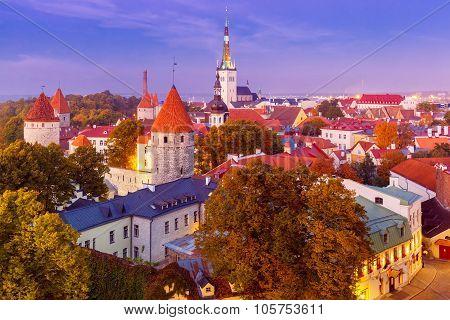Aerial cityscape with Medieval Old Town, St. Olaf Baptist Church and Tallinn City Wall illuminated in autumn twilight, Tallinn, Estonia poster
