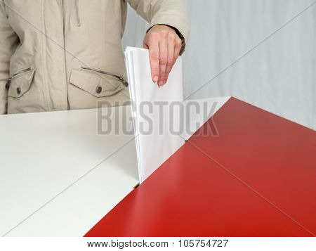 Voter casting a vote into ballot box during election to the Polish Parliament poster