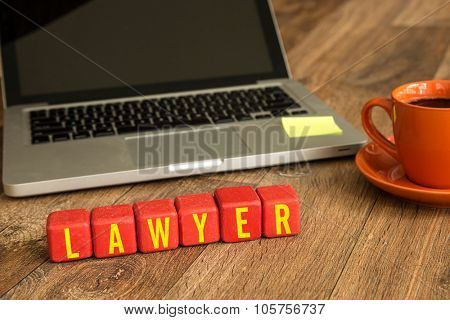Lawyer written on a wooden cube in front of a laptop