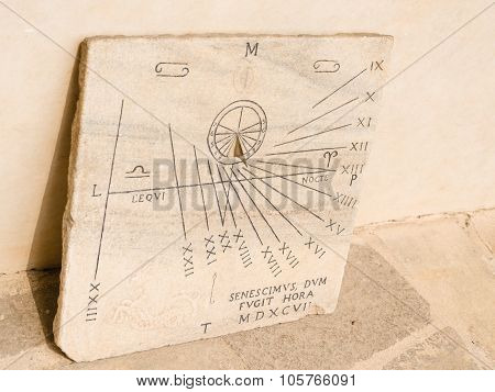 view of a middle ages sundial leaning against a wall poster