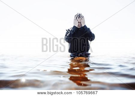 Young man experiencing the pain and disappointment, water through fingers
