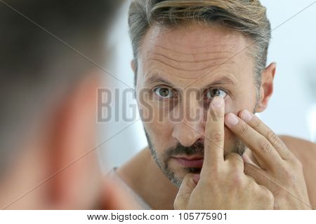 Closeup of middle-aged man insterting contact lens