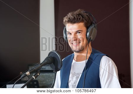 Portrait of smiling young male singer in recording studio poster