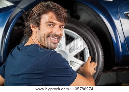 Portrait of happy mechanic fixing hubcap to car tire at garage