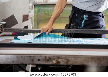 Midsection of male worker designing paper in factory