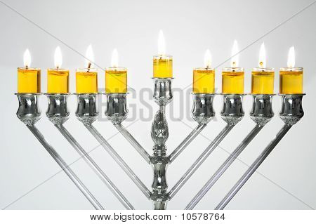 Silver Hanukkah candles with oil candles all candles lite on the traditional Hanukkah menorah poster