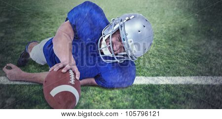 American football player struggling to catch the ball against rugby pitch