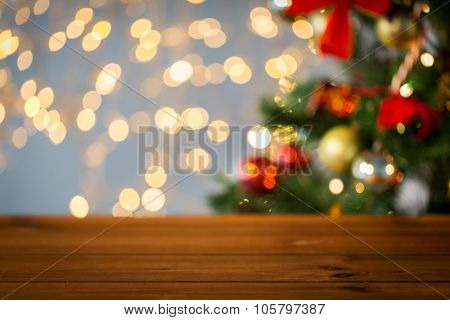 holidays, new year and celebration concept - close up of empty wooden surface or table over christmas tree and lights background