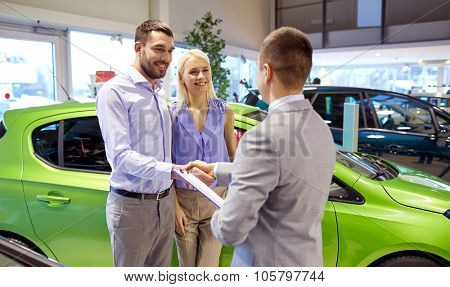 auto business, car sale and people concept - happy couple with dealer shaking hands in auto show or salon