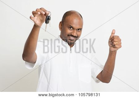 Portrait of Indian man holding new house key and thumb up, real estate property agent concept, standing on plain background with shadow.