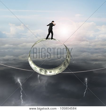 Businessman Standing On Roll Of Dollar Bills Balancing Tightrope