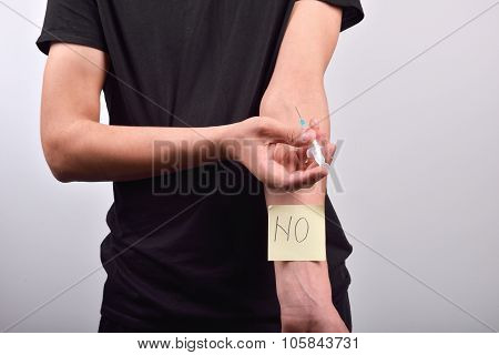 Hand with heroin syringe with post it that says NO. The concept of not starting to use drugs poster