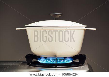 white cast iron saucepan on the gas stove