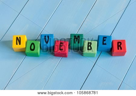 November sign on color wooden cubes with light blue wood background.