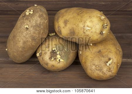 Freshly harvested organic potatoes on a wooden table. Growing domestic vegetables