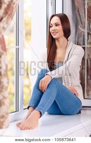 Feeling content. Full length and selective focus of attractive young lady who is sitting on the windowsill and smiling pleasantly while looking out of the window. poster